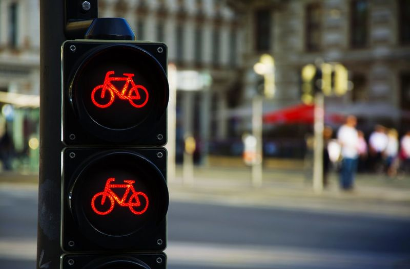 Close-up of illuminated bicycle sign on road signal by city street