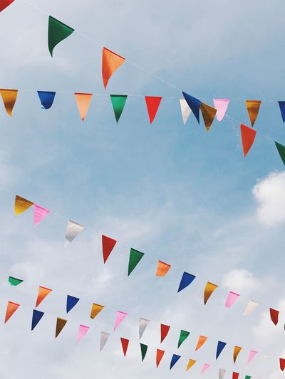 Blue Bunting Celebration Cloud - Sky Day Decoration Flag Hanging In A Row Large Group Of Objects Low Angle View Multi Colored Nature No People Outdoors Shape Sky Streamer String Triangle Shape White Color