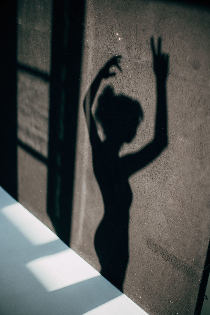 Shadow of woman with arms raised falling on wall