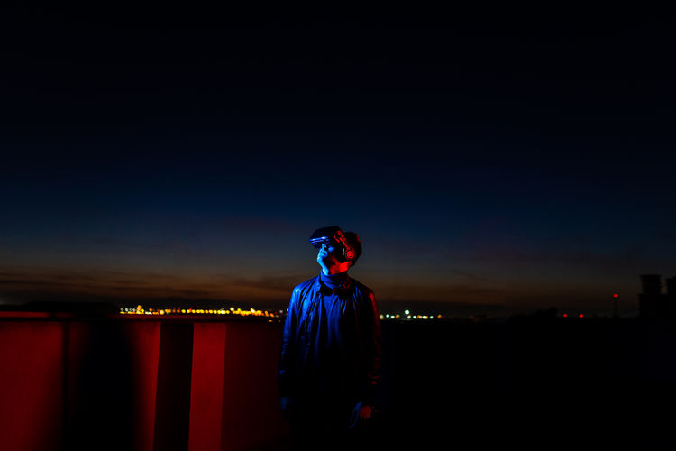 Side view of young man standing against illuminated blue sky at night