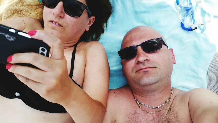 Woman with man using mobile phone at beach