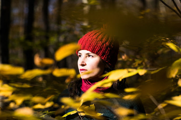 Young Woman Looking Away Amidst Leaves