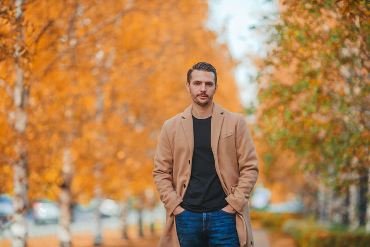 Portrait of young man standing against trees during autumn