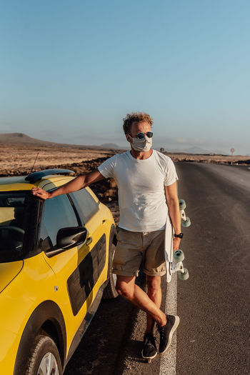 Full length of man standing by car against clear sky