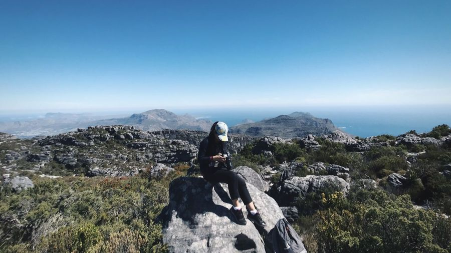 on the top of table mountain Destination Traveling Cape Town South Africa Travel Photography Woman In Nature Lost in the Landscape Sitting Asian  World Herritage Table Mountain On The Top Of The Mountain Sky Nature Mountain Lifestyles One Person Real People Leisure Activity Scenics - Nature Beauty In Nature