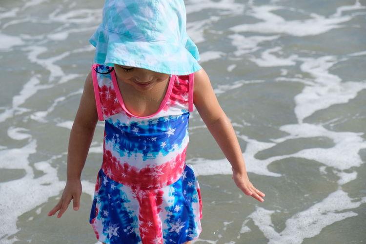 Full length of girl playing in beach