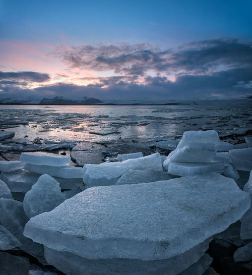 Colorful sunset landscape in Jokulsarlon glacier lagoon in Iceland with ice chunks and mountains Jökulsárlón Jökulsárlón Nordic Countries Nature Ice Beauty In Nature Landscape Sea Water Snow Cold Temperature Frozen Water Sunset Beach Wave Polar Climate Winter Dramatic Landscape Iceberg - Ice Formation Natural Landmark Lagoon Glacier Iceland Visual Creativity