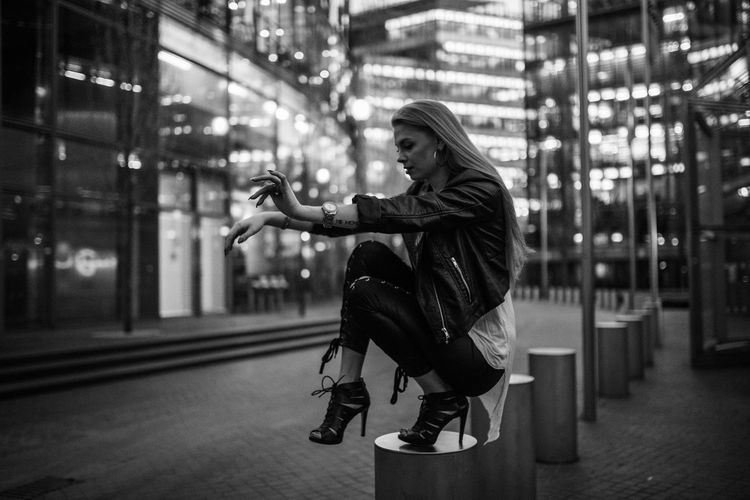 Young woman crouching on bollard in city at night