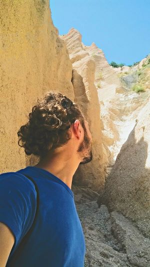 Side view of young man standing by rock formations during sunny day