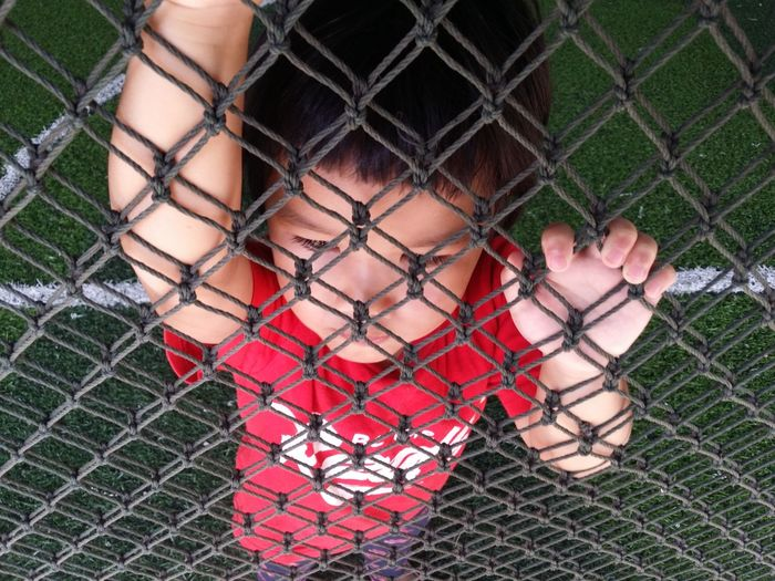 High Angle View Of Boy Lying On Playing Field Seen Through Net