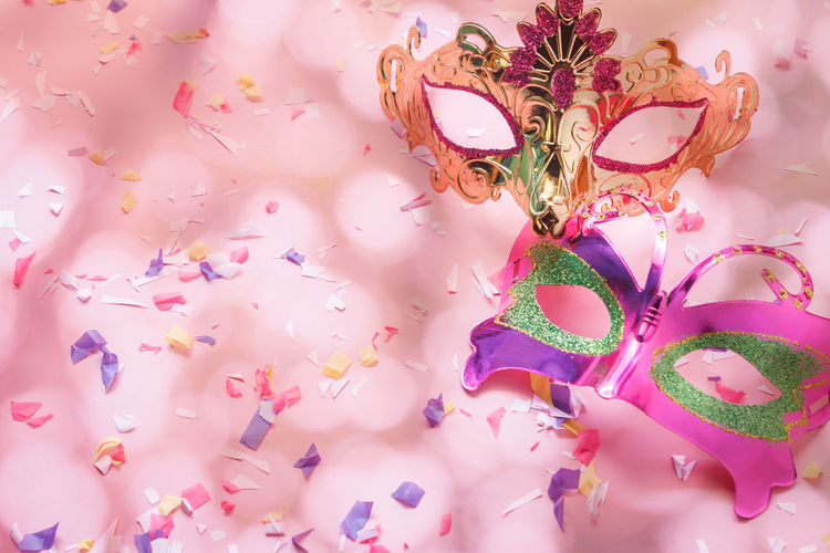 Close-up of multi colored masks and confetti on table