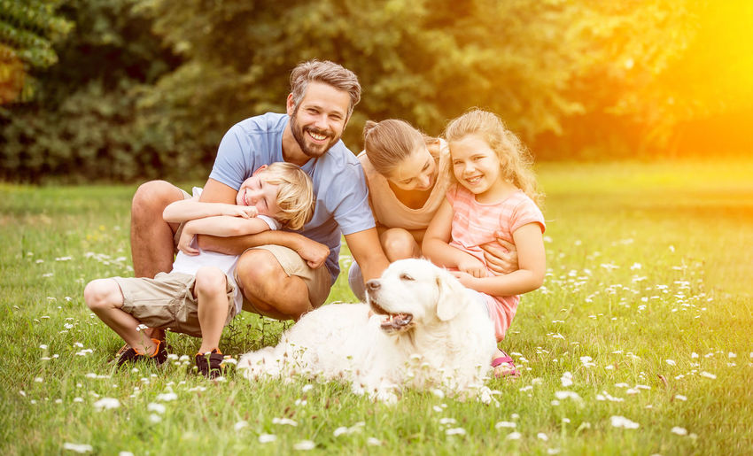 Cheerful Family With Dog At Park