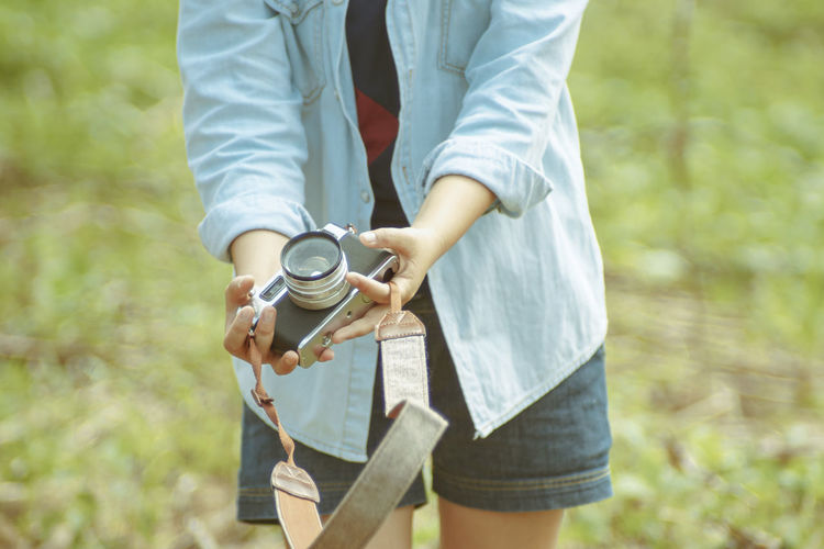 Midsection of woman holding camera while standing on field