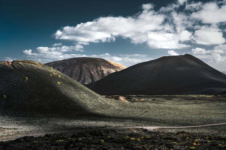Scenic view of volcanic craters against cloudy sky