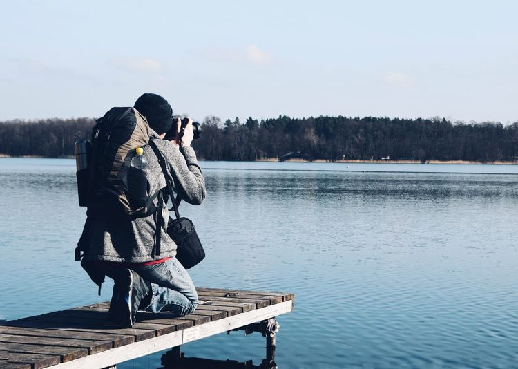 Man photographing while kneeling on pier over lake against sky