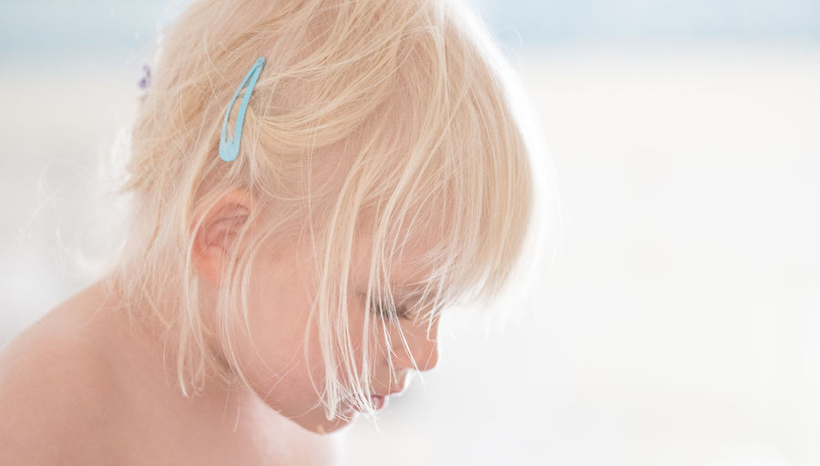 Cropped image of girl with short blond hair against sky