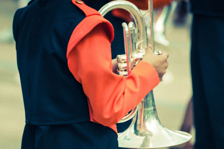 Silver Trumpet Musical Instrument Music Sound Adult Close-up Clothing Day Focus On Foreground Glass Hand Holding Human Hand Incidental People Instrument Lifestyles Men Midsection Musical Instrument One Person Real People Silver Colored Standing Trumpet Player Uniform