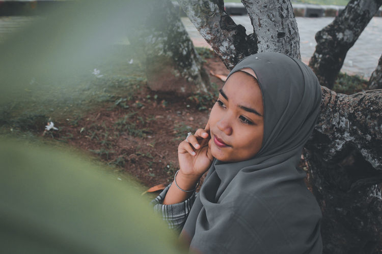 High angle view of thoughtful young woman wearing hijab sitting outdoors