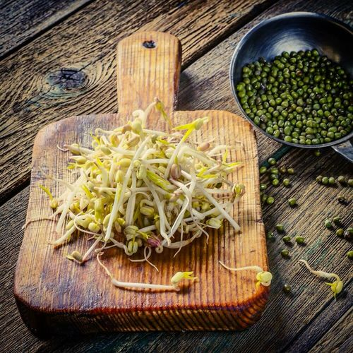 High Angle View Of Bean Sprouts With Cutting Board On Table