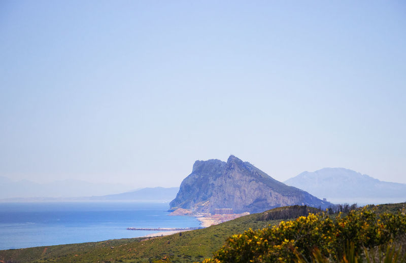 Scenic view of sea and gibraltar against clear blue sky