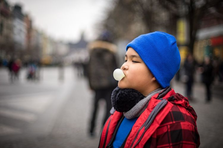 Side view of boy blowing bubble gum on city street