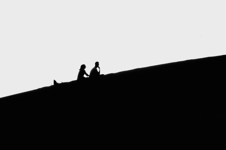 Low angle view of silhouette people standing on land against clear sky