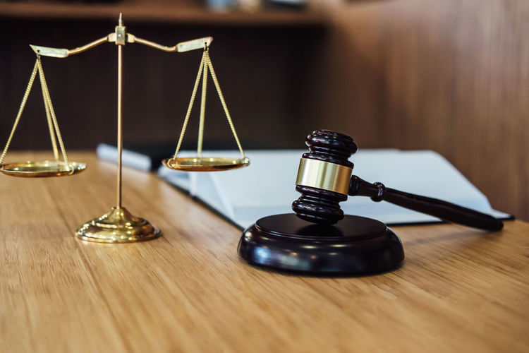 Indoors  Weight Scale Law Balance No People Focus On Foreground Wood - Material Close-up Legal System Scale  Justice - Concept Still Life Stack Accuracy Social Issues Mass - Unit Of Measurement Metal Courthouse Courtroom Legal Verdict Jurisprudence Gavel Lawyer Fairness