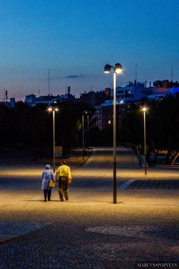 Título: Noche de verano/Summer night. Autor: Marcus Populus Lugar: Madrid Río Cámara: Panasonic DMC TZ60 Punto F: f/4.8 Tiempo de exposición: 1/8s Velocidad ISO: 1600 Distancia focal: 15mm City Illuminated Lighting Equipment Night Real People Sky Street Street Light Two People