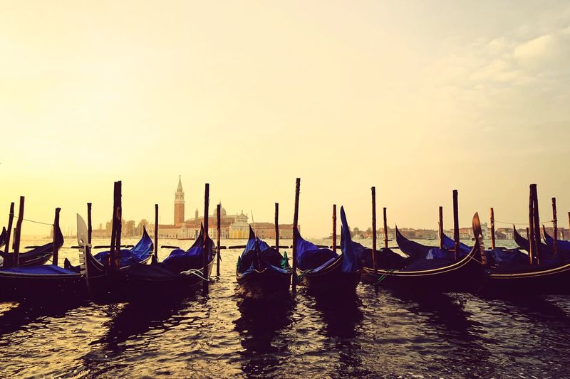 Gondolas moored at grand canal against sky during sunset
