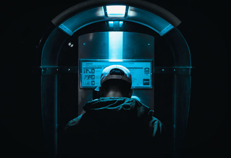 Rear view of man using pay phone at night