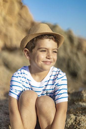 Cute boy wearing hat sitting on rock
