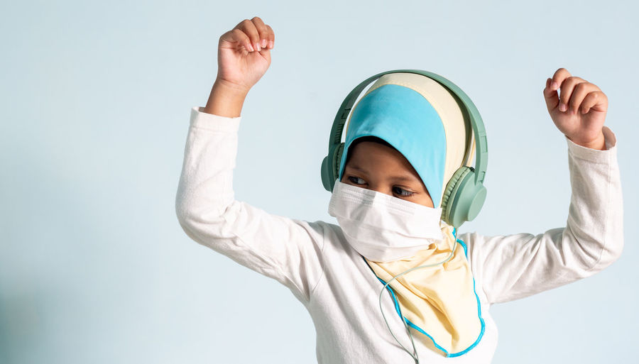 Portrait of boy with arms raised against white background