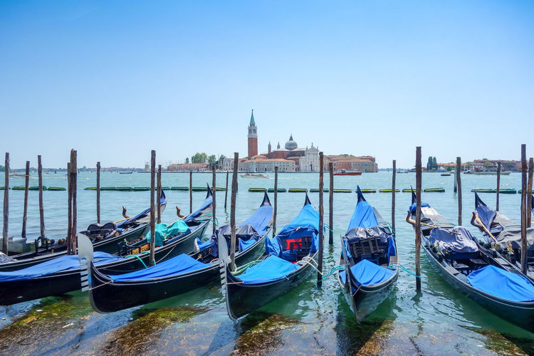 Gondolas moored on grand canal by church of san giorgio maggiore against clear sky