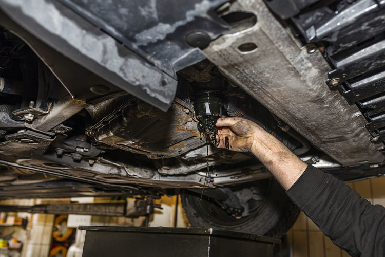 The car mechanic unscrews the diesel oil filter located in the oil pan, you can see the old oil.
