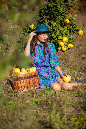 Woman with fruits sitting on land
