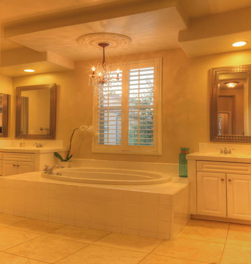 Oval hot tub spa bathtub in a marble bathroom with feng shui decor and chandelier. Architecture Bathtub Chandelier Crown Molding Hot Tub Illuminated Indoors  Interior Design Light Luxury Marble No People Plantation Shutters Relaxing Sink Tranquility Vertical