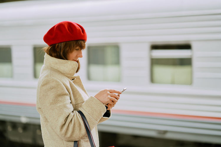 Side view of woman using phone while standing at railroad station