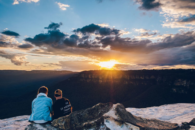 Rear view of people sitting on mountain against sky during sunset