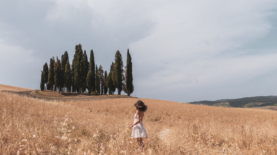 Woman standing on field against sky in tuscany