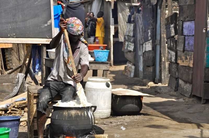 African Ghana Shanty Town Africa Bucket Business Container Developing Country Food Fufu Full Length Men Occupation One Person Outdoors Poverty Preparing Food Protective Workwear Real People Shanty Slum Social Issue Social Issues Working Stack Working Adult