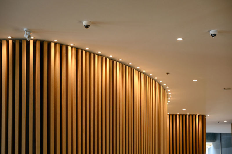 Low angle view of illuminated lights on ceiling of building