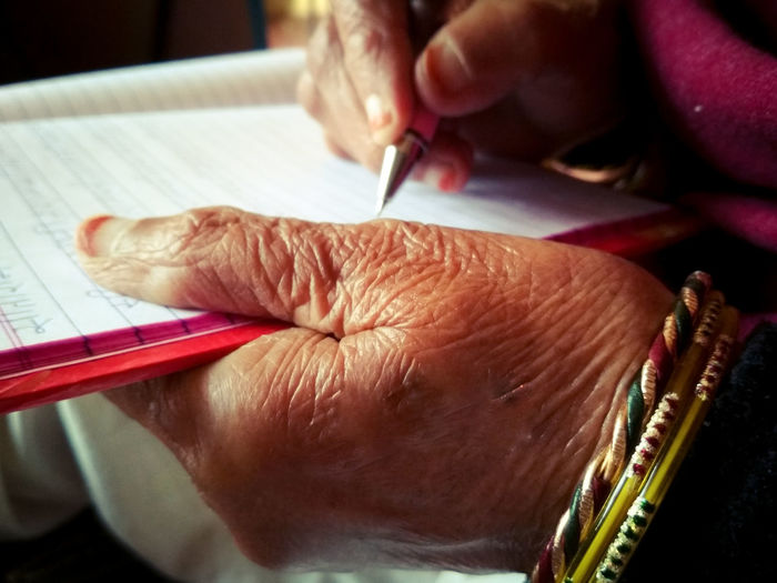Cropped Image Of Woman Writing In Book