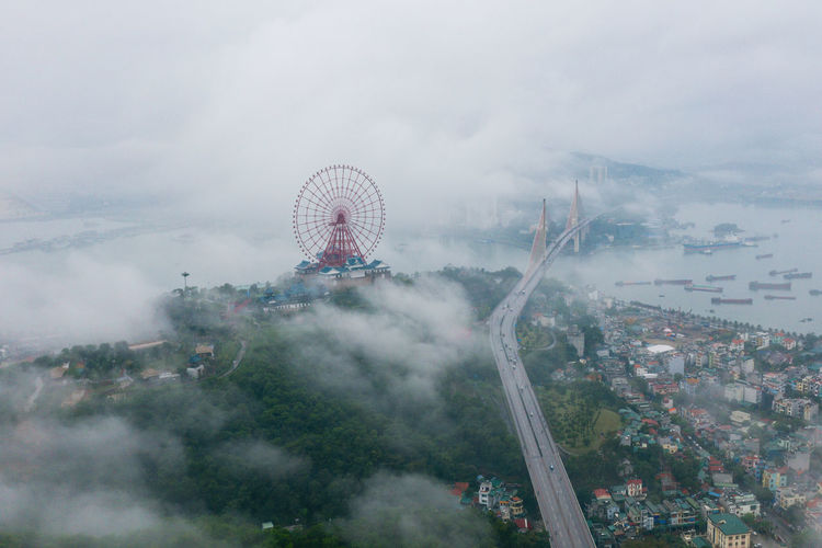 Aerial view of ferris wheel and bridge in city during foggy weather