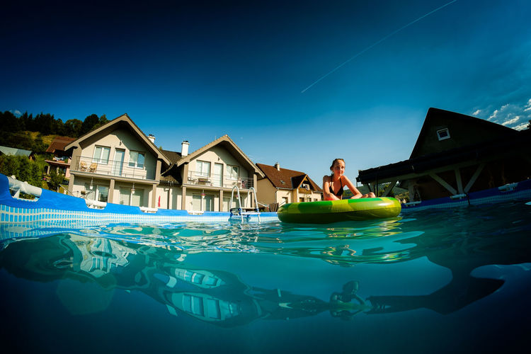 Girl With Inflatable Ring Floating On Wading Pool At Tourist Resort Against Blue Sky