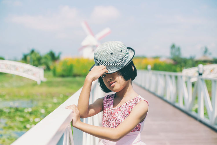 Young woman wearing hat standing against sky