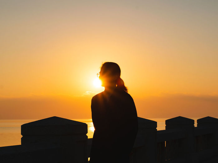 Silhouette woman standing by railing against orange sky