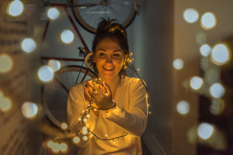 Smiling Young Woman Holding Illuminated String Lights