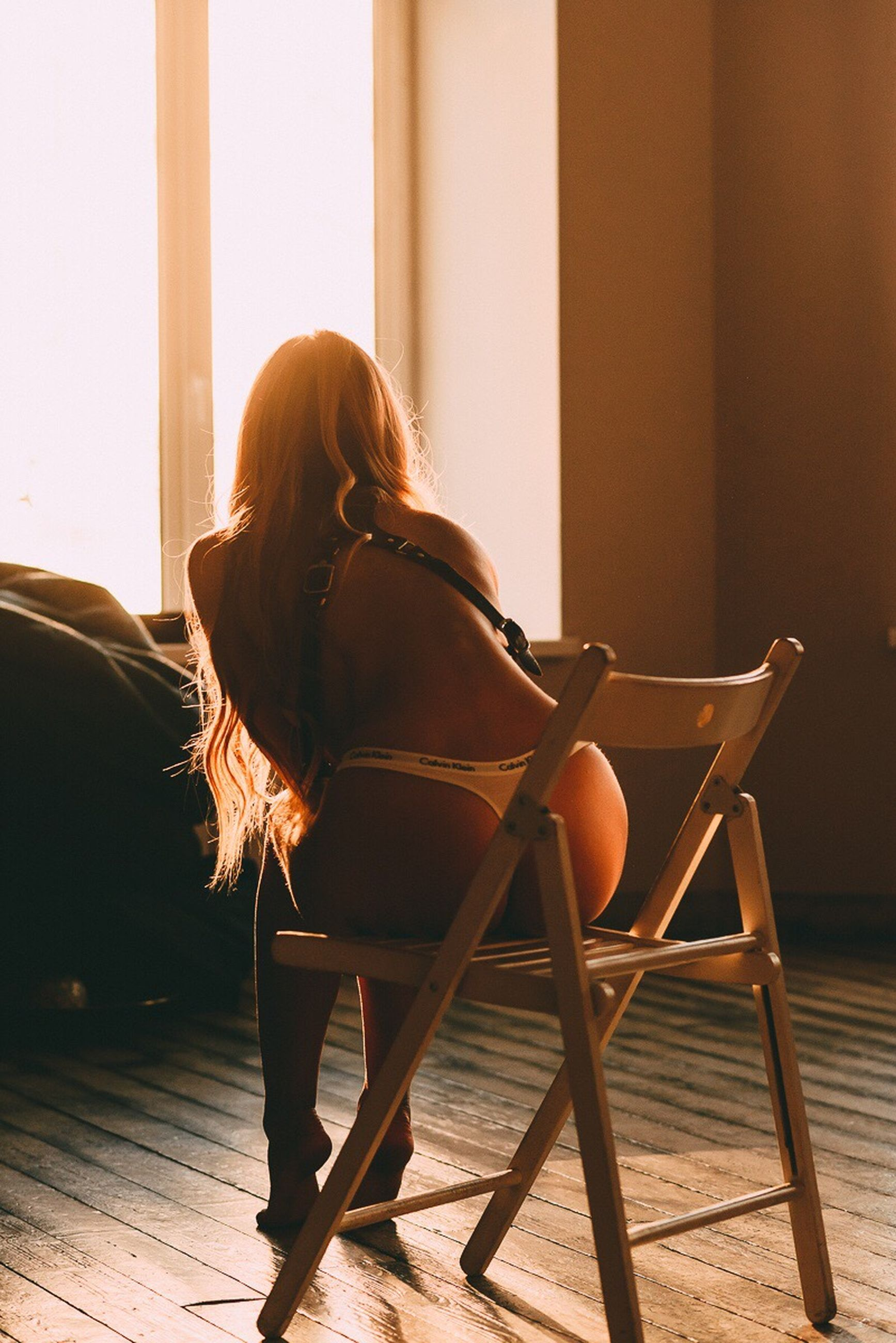 one person, real people, sitting, long hair, indoors, rear view, chair, full length, leisure activity, lifestyles, young adult, women, day, young women, people