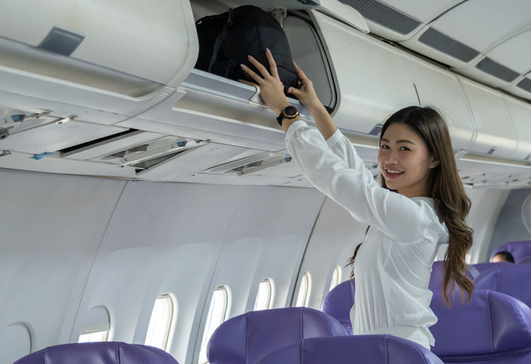 Young woman sitting on seat in airplane