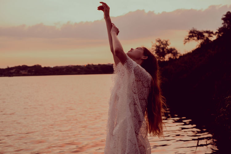 Woman standing in water at sunset